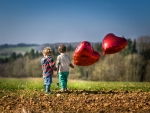 Children with balloons in a field