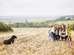 family in field with dog