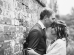 bride and groom kiss by wall